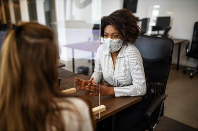 A masked employee helping a client during the COVID-19 pandemic.