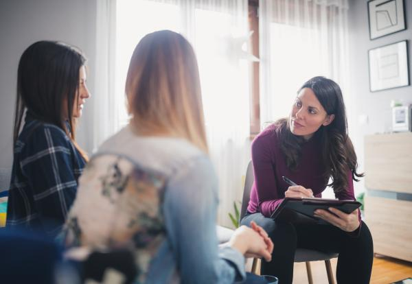 A financial professional in a meeting with two clients.
